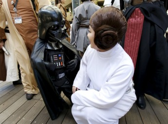 "Cosplayers dressed up as ""Star Wars"" characters Darth Vader and Princess Leia talk at a Star Wars fan event in Tokyo"